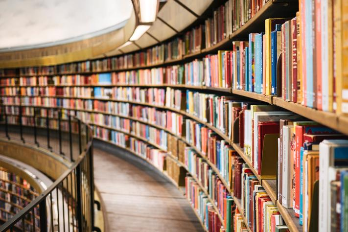 A picture of a library with a big curved wall of books